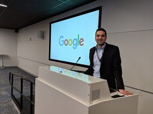 TZHS alumnus Edward Forgacs standing at white podium with Google sign behind him