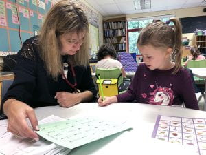 Female teacher helping student with writing