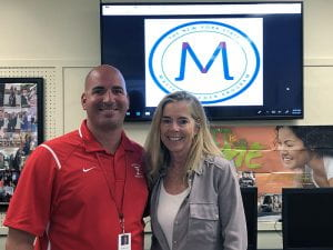 Tappan Zee High School's NYS Master Teachers Steve Cohn and Karen Connell, smiling in front of TV with NYSMTP logo