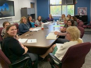 Clerical staff smiling and seated around conference table
