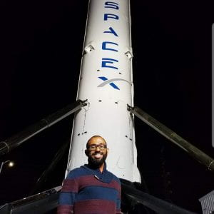Joval Mathew ('12) in front of SpaceX rocket