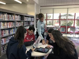 Library Media Specialist Patty Eyer works with group of students in TZHS Library
