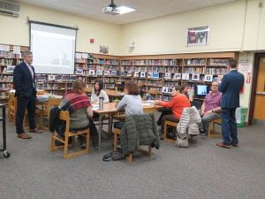 SOMS administrators, standing, speak to small group of seated parents in library