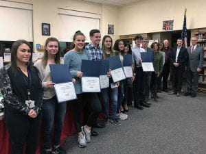 District administrators, board members and students holding certificates standing in line