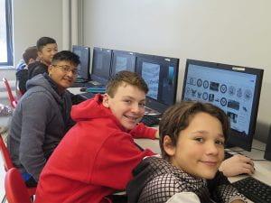 DDP students at desktops, smiling
