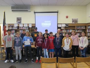 VFW members and essay contest winners posing in library
