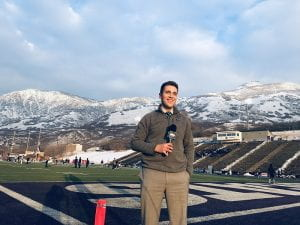 Andrew Badillo with mic at sports event with snowy mountains in background