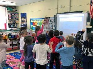 Teacher showing children the letter W.