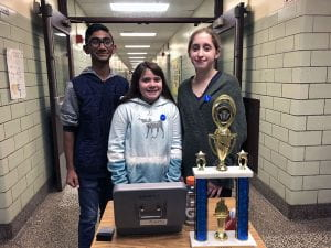Three students in hallway with cash box and trophy