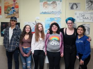 Students standing in front of art work.