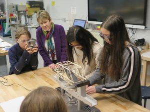 Teacher and students looking at bridge and structure tester