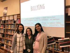 "School Prevention Counselors and FEC Coordinator in SOMS library with ""Bullying"" presentation on screen"