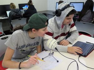 Students sitting at desk in front of computer and microphone.