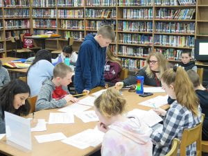 Students sitting around table with teacher in library.