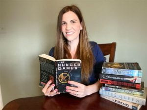 Stephanie Stehly with stack of dystopian novels