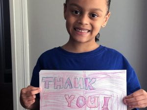"""Student smiling with """"thank you"""" sign"""