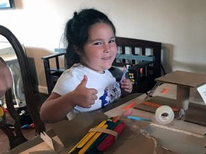 STEAM Camper gives thumbs up during cardboard construction project