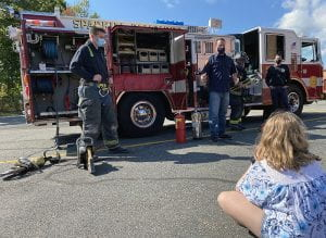 Firefighters talk to student seated on ground