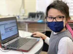 Female student coding on laptop