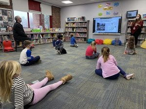 Students sitting on floor looking at smartboard