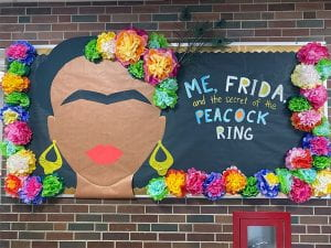 """Bulletin board with """"Me, Frida and the Secrety of the Peacock Ring"""" artwork"""