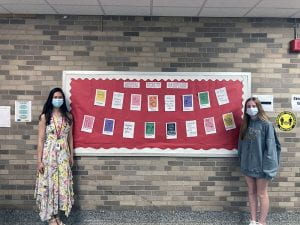 Student and teacher posing in front of bulletin board of hashtag projects
