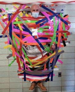 Principal taped to wall