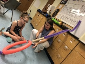 Teacher helps camper with marble rollercoaster design