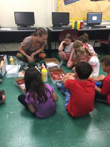 Students gathered in a circle to dive into a hands-on project at Summer STEAM Camp in July 2017.