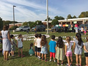 Music teacher Bet Fox leads students in peace song singalong as teachers hold up word cards at WOS Pinwheels for Peace ceremony