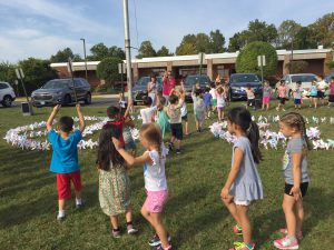 "WOS students show ""peace"" after their Pinwheels for Peace ceremony"