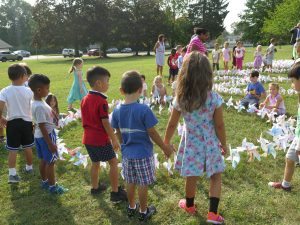 WOS students, holding hands, admire pinwheels at school Pinwheels for Peace art installation