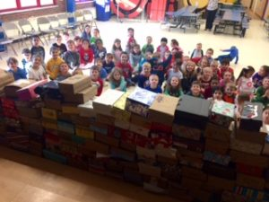 William O. Schaefer Elementary School students with large pile of shoeboxes filled with emergency foodstuffs