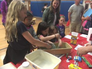 children with hands in oobleck tub at family fun science night