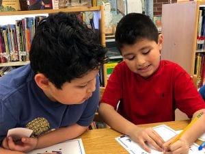 Two boys working on word puzzle