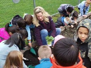 Blonde woman working in garden with elementary school children wearing coats