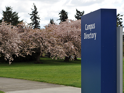 "Blue sign that reads ""Campus Directory"" with grassy lawn and flowering trees in background"