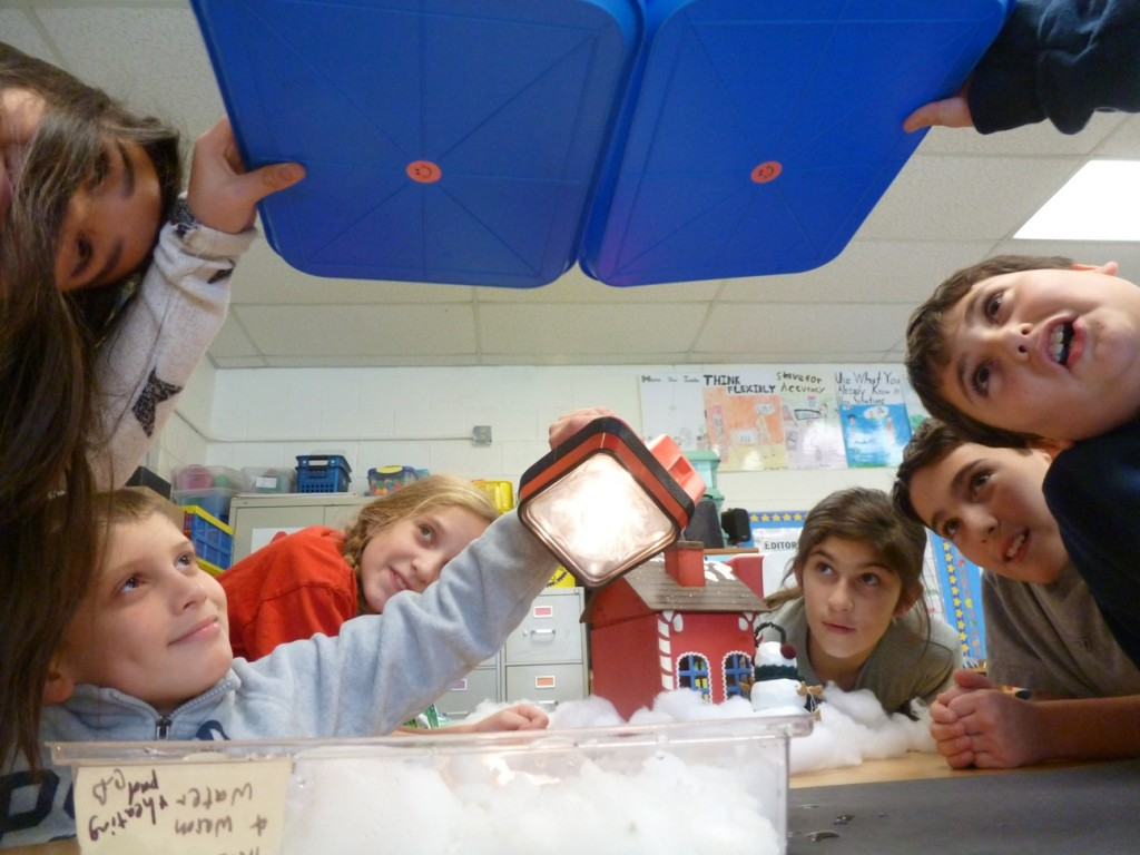 When the classroom light is turned off, the students could see the light of the flashlight reflect off the snow and shine on the bottom of the trays.
