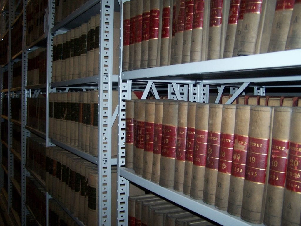 Shelves of bound volumes of records at the City of Boston Archives.