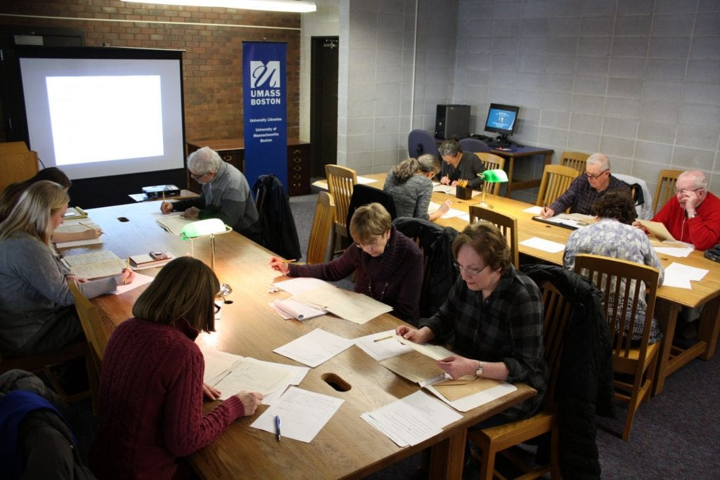 Group of people sit at wooden tables examining archival documents.
