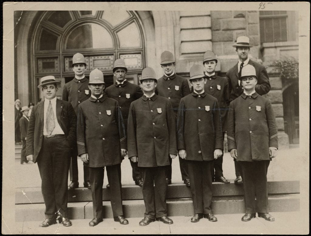 Black and white photo of police officers in uniform.