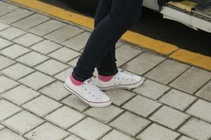 feet walking on pavement in sneakers