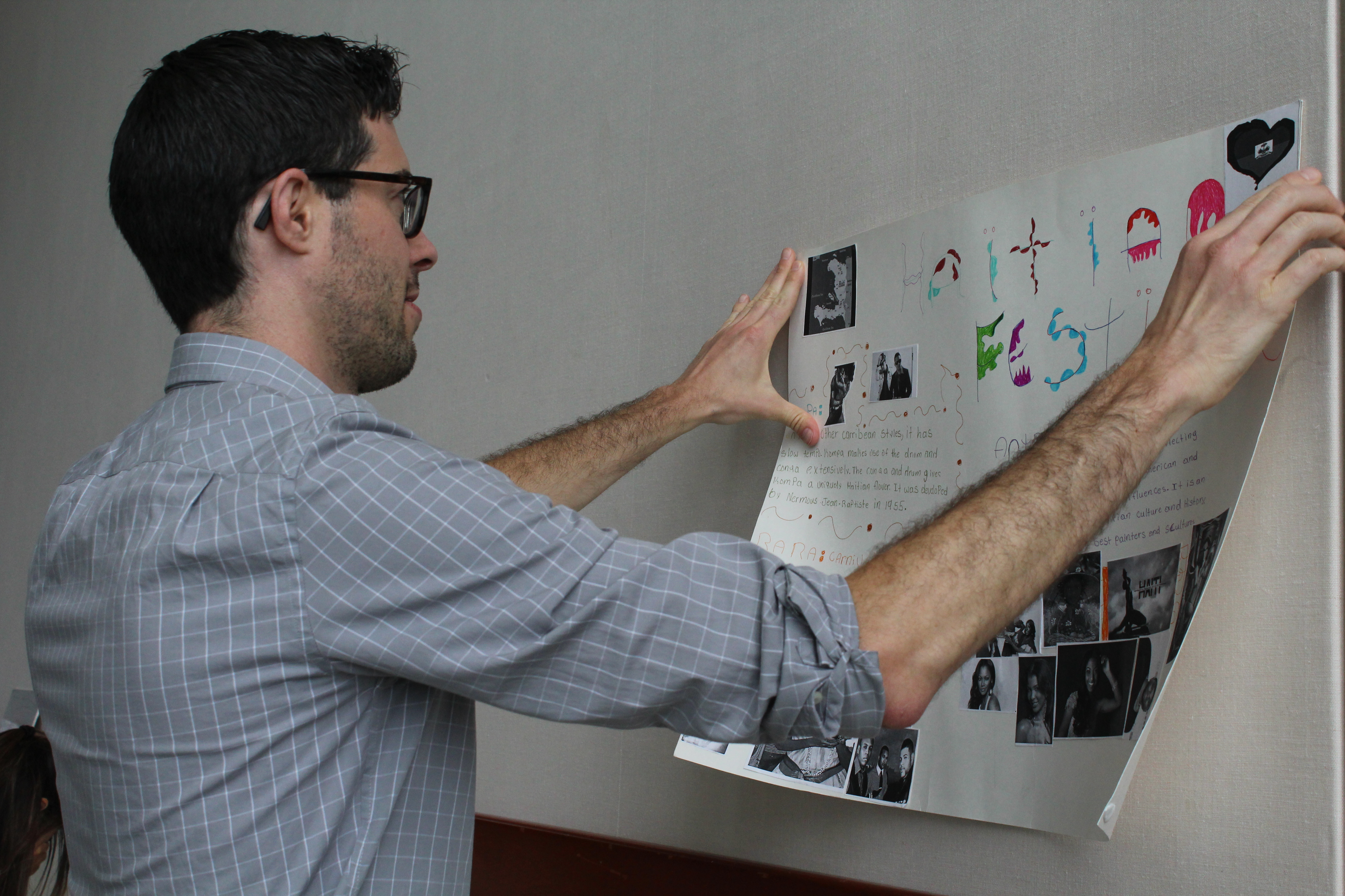 Jeff helps hangs student poster on the wall.
