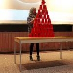 A blue team captain takes on Stack Attack challenge for a minute, although she able to only successfully to stack the cup into a pyramid shape.