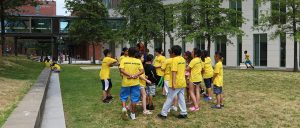 Students stand around in circle in their yellow ALERTA shirts