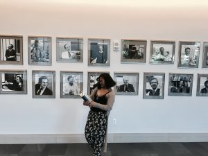 Anny, the Web Publishing Intern is standing in front of the portraits of law professors in the halls of Harvard Law School with her clipboard and notebook.