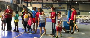 Students line up along the gym lines with their mentors in the read t-shirt.