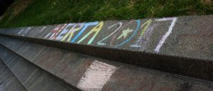 """Alerta 2017"" printed in yellow, blue, red and green chalk on cement stairs"