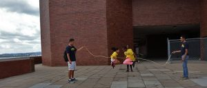 Two students jump rope together in the middle while mentors stand on the side holding up rope