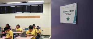 """The left half of the classroom shows half of an ALERTA classroom with the students in their yellow t-shirts. The right half of the photos shows a purple door with a piece of paper that says """"Green Stars"""" with name of teacher, TA and a icon of a green star."""